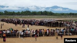 Rohingya refugees line up to receive food at a camp near Teknaf, Bangladesh, Oct. 12, 2017.