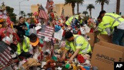 FILE - Workers remove a makeshift memorial honoring the victims of the Oct. 1 mass shooting, Nov. 12, 2017, in Las Vegas.