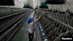 FILE- A woman works at a yarn-weaving plant of the Ha Nam textile company in Phu Ly city, about 60 km (37 miles) south of Hanoi, July 4, 2013.