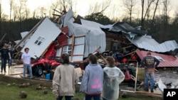 La gente examina los daños causados por una tormenta al sur de Mount Olive, en Mississippi, el lunes, 2 de enero, de 2017.