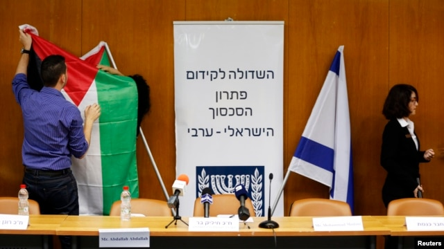 FILE - Israeli parliament employees set up a Palestinian and Israeli flag ahead of a meeting between Israeli parliament members and a delegation of Palestinian politicians and businessmen aimed at encouraging Israeli-Palestinian negotiations, at the Knesset, the Israeli parliament, in Jerusalem, July 31, 2013.