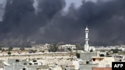 Bầu trời thủ đô Tripoli tràn ngập khói đen trong lúc tiếng súng và các vụ nổ vẫn tiếp diễn chung quanh khu dinh thự Bab Al-Aziziya của ông Gadhafi và nhiều nơi khác trong thành phố, ngày 23/8/2011