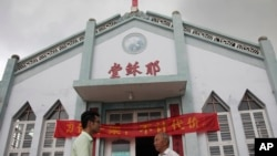 "FILE - In this photo taken July 15, 2014, Pastor Tao Chongyin, left, speaks with church member Fan Liang'an in front of the Wuxi Christian Church with the words ""Church of Jesus"" in red in Longwan, Wenzhou in eastern China's Zhejiang province."