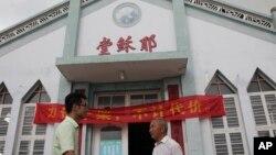 """Pastor Tao Chongyin (kiri) bersama anggota gereja Fan Liang'an di depan Gereja Kristen Wuxi bertuliskan """"Gereja Yesus"""" di Longwan, Wenzhou, Provinsi Zhejiang, bagian timur China, 15 JUli 2014 (Foto: dok)."""