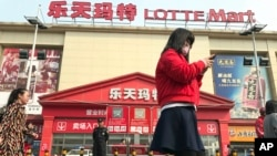 Residents walk past a Lotte Mart where additional security measures are visible in Beijing, China, March 17, 2017. Retail giant Lotte Group, South Korea's No. 5 business group, took the brunt of the backlash after agreeing to let one of its golf courses in southeastern South Korea be a site for deploying the Terminal High-Altitude Area Defense system, or THAAD. At least 55 of 99 Lotte Mart discount stores in China were shut in early March for a month each after surprise inspections found violations of fire safety standards.