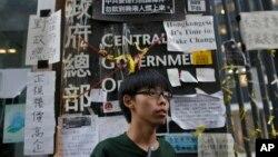 """香港学民思潮召集人黄之锋在香港政府总部前面。一个名为""""匿名""""(Anonymous)的网上团体威胁攻击香港政府网站"""