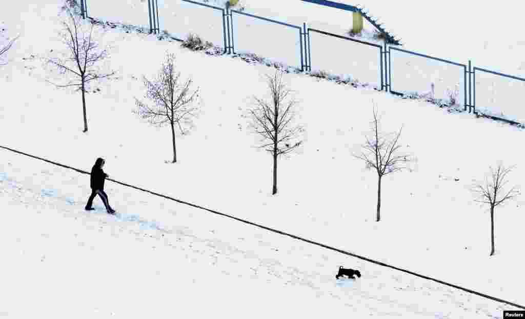 Beyaz Rusya Minsk'te köpeğiyle karda yürüyen adam