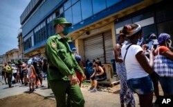Seorang tentara menjaga keamanan saat warga antre untuk membeli bahan-bahan pangan di Havana, Kuba (foto: dok).