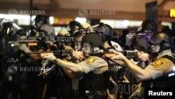 Ajan polis ki pwente zam yo sou manifestan ki tap pwoteste pou yo denonse lanmò pa bal jenn nwa ameriken Michael Brown nan vil Ferguson. (Foto: 18 out 2014).