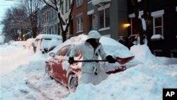 Una mujer palea la nieve cubre su auto y la entrada a la casa en Albany, Nueva York.