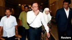 Nhà lãnh đạo đối lập Malaysia Anwar Ibrahim (giữa) và vợ đến tòa án ở Putrajava, Malaysia 7/3/14