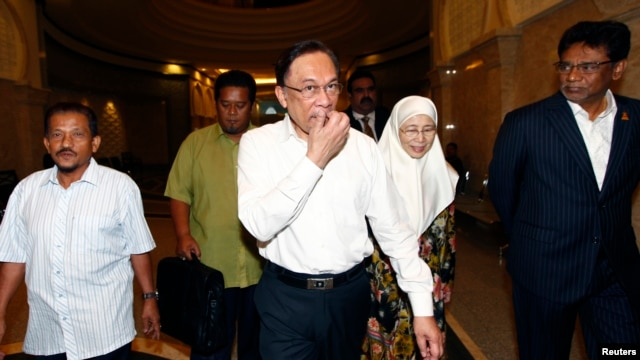 Malaysian opposition leader Anwar Ibrahim (C) and his wife Wan Azizah arrive at a court house in Putrajaya, March 7, 2014.