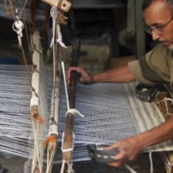 A Palestinian man uses a loom to weave carpets in Gaza City.
