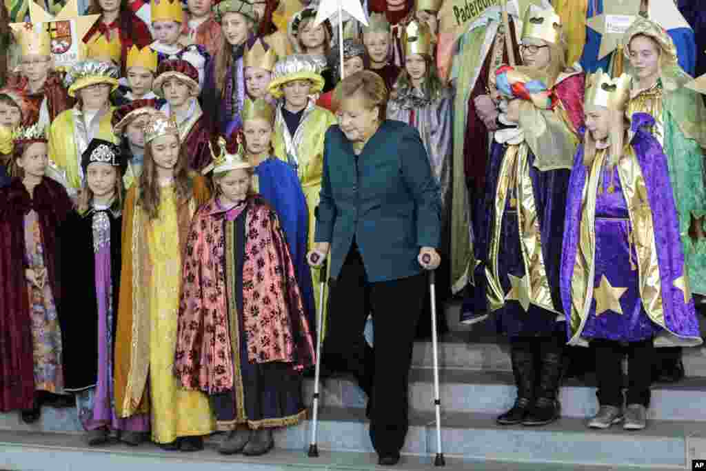 German Chancellor Angela Merkel uses crutches as she attends the annual reception for Carolers at the chancellery in Berlin. Merkel suffered a pelvis injury during ski holidays in the Swiss Alps and will have to cut back on her work schedule for the next three weeks.