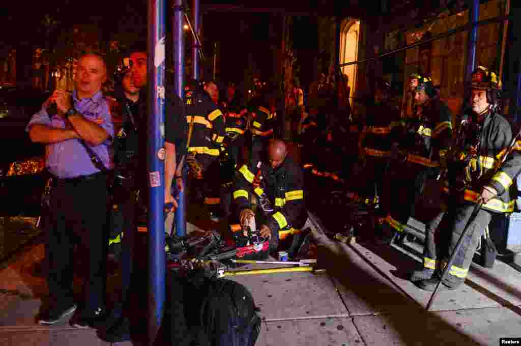 New York City firefighters stand near the site of an explosion in the Chelsea neighborhood of Manhattan, Sept. 17, 2016.