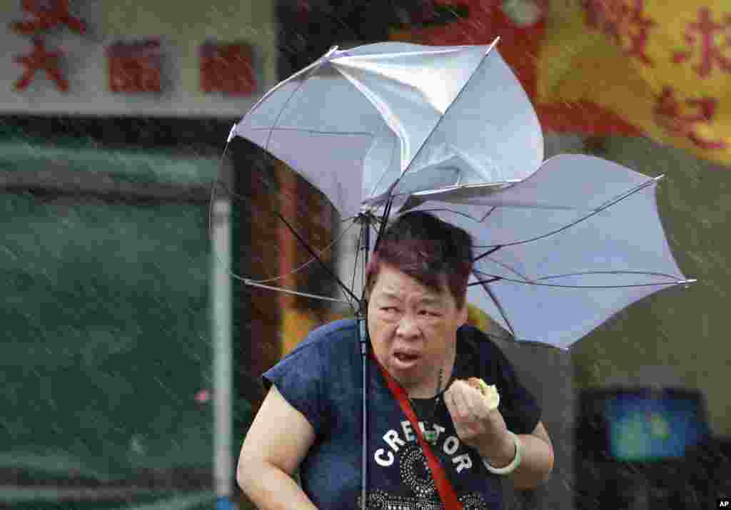 A woman struggles with her umbrella against powerful gusts of wind generated by typhoon Megi across the the island in Taipei, Taiwan. Schools and offices have been closed in Taiwan and people in dangerous areas have been evacuated as a large typhoon with 162 kilometers- (100 miles-) per-hour winds approaches the island.