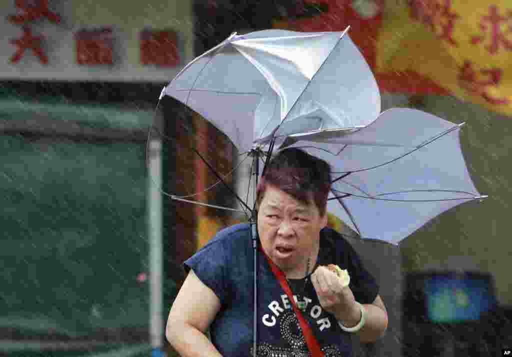 د تایوان د ټایپي ښار له یوه سړک څخه یوه ښځه د تیریدو په حال کې چې په کې قوي باد لګیږي.