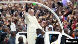 Pope Francis waves to the faithful as he arrives for a Mass in Kenya's capital, Nairobi, Nov. 26, 2015.