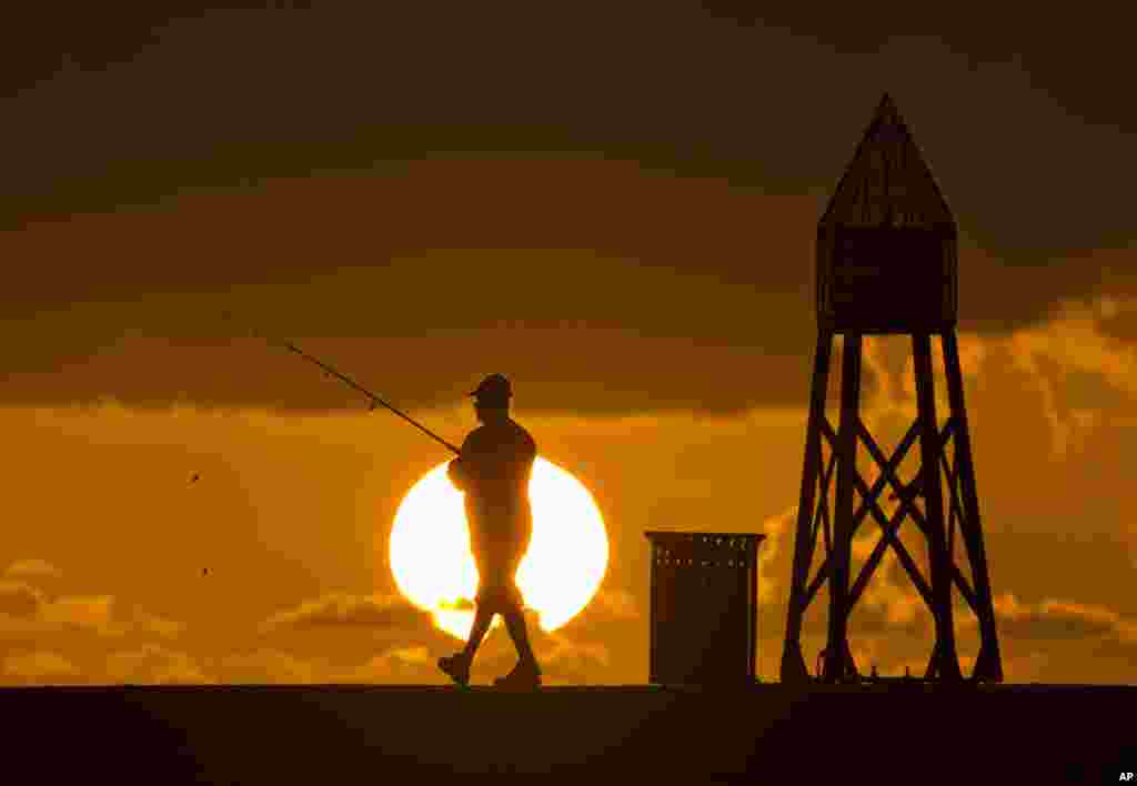 A fisherman prepares to cast a line as the sun rises behind him as he fishes off a jetty into the Atlantic Ocean in Bal Harbour, Florida.