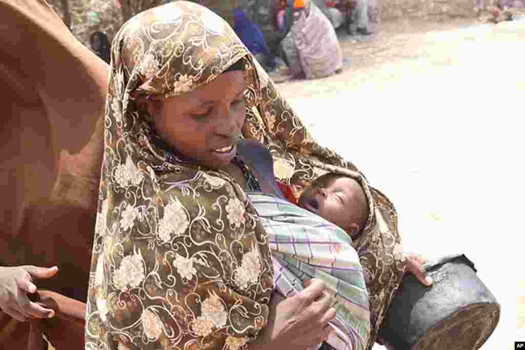 Woman carrying baby asleep going to get food at Badbaado IDP camp in Mogadishu, Somalia, August 11, 2011. (VOA - P. Heinlein)