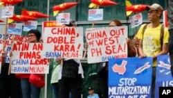 Polisi menjaga pintu masuk ke Konsulat China saat aktivis lingkungan memprotes dugaan pembangunan militer China pada pulau-pulau yang disengketakan di Laut Cina Selatan, 24 Januari 2017 di distrik keuangan Makati timur dari Manila. (AP Photo/Bullit Marquez)