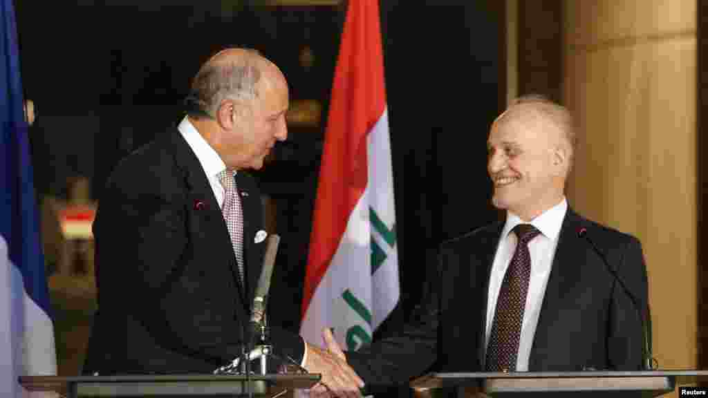 French Foreign Affairs Minister Laurent Fabius, left, shakes hands with Iraq's Deputy Prime Minister for Energy Hussain al-Shahristani after a news conference in Baghdad, Iraq, Aug. 10, 2014.