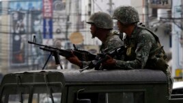 Members of the Philippine Marines hold their weapons aboard a truck as they block a road during fighting between government soldiers and Muslim rebels of Moro National Liberation Front (MNLF) in Zamboanga city in the southern Philippines September 15, 2013.