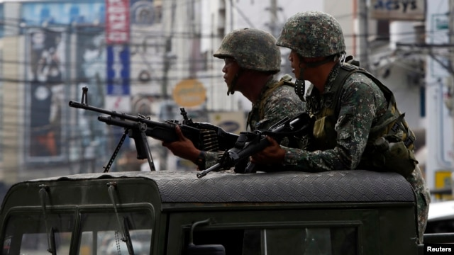 Members of the Philippine Marines hold their weapons aboard a truck as they block a road during fighting between government soldiers and Muslim rebels of Moro National Liberation Front (MNLF) in Zamboanga city in southern Philippines, Sept. 15, 2013.