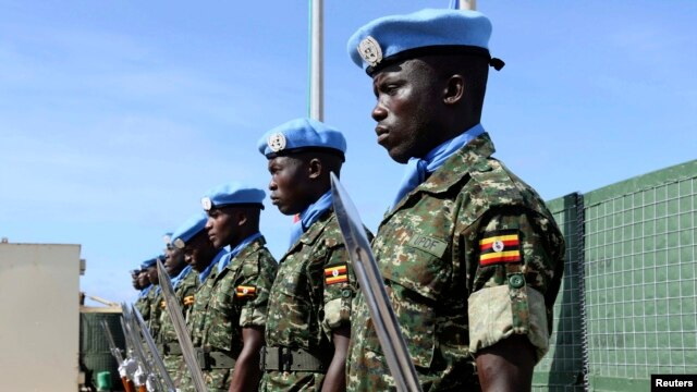 FILE - Ugandan peacekeeping troops stand during a ceremony at Mogadishu airport in Somalia.