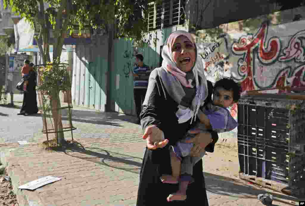 A woman cries as Palestinians flee their homes after Israel airdropped leaflets warning people to leave the area, in the Shajaiyeh neighborhood of Gaza City, July 16, 2014.