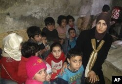 This March 11, 2018 photo, provided by Deana Lynn, from Detroit, Michigan, shows her, with her kids and other Syrian children at a shelter where they hide from Russian and Syrian government forces airstrikes, in eastern Ghouta, a suburb of the Syrian capital Damascus.