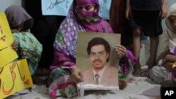 Safia Bano - didampingi anggota keluarga lainnya, hari Minggu (18/9) di kota Burewala, Pakistan -membawa poster bergambar foto suaminya Imdad Ali, terpidana mati yang akan menjalani eksekusi hari Selasa (20/9) setelah pengajuan bandingnya ditolak Mahkamah Agung.