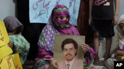 Pakistan Execution: Safia Bano displays the picture of her husband Imdad Ali, a death row prisoner, while she sits with other family members in Burewala, in central Pakistan, Sunday, Sept. 18, 2016.