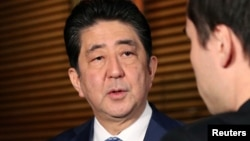 FILE - Japan's Prime Minister Shinzo Abe speaks to reporters about North Korea's missile launch, in Tokyo, Japan in this photo taken by Kyodo, Nov. 29, 2017.