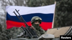 FILE - A Russian flag is seen behind a Russian army vehicle.
