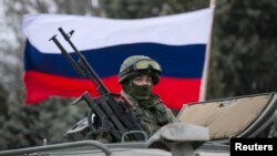 FILE - A Russian flag is seen behind a Russian army vehicle outside a Ukrainian border guard post in the Crimean town of Balaclava March 1, 2014.