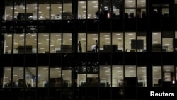 FILE - Workers are seen in office windows in the financial district of Canary Wharf in London, Nov. 3, 2015.