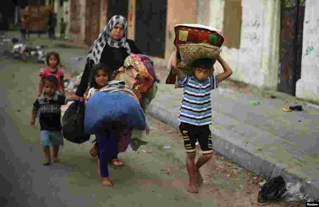 Palestinians carry their belongings as they flee Israeli airstrikes, in Gaza City, July 29, 2014.