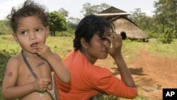 An ethnic minority Cambodian boy, left, stands next to his mother at a village in Mondolkiri province some 265 kilometers (165 miles) northeast Phnom Penh, file photo.
