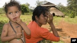 An ethnic minority Cambodian boy, left, stands next to his mother at a village, file photo.
