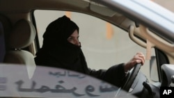 FILE - Aziza Yousef drives a car on a highway in Riyadh, Saudi Arabia, March 29, 2014, as part of a campaign to defy Saudi Arabia's ban on women driving. Carmakers hoping to sell more cars in Saudi Arabia are applauding the king's order to draw up new rules allowing women to drive.