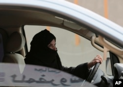 FILE - Aziza Yousef drives a car on a highway in Riyadh, Saudi Arabia, March 29, 2014, as part of a campaign to defy Saudi Arabia's ban on women driving.
