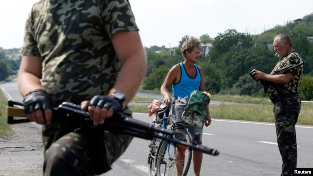 Armed pro-Russian separatists stop a resident at a checkpoint outside Donetsk, Aug. 5, 2014.