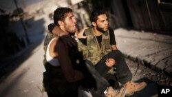 Hai người lính thuộc phe nổi dậy Syria giúp một người bị thương trong quá trình chiến đấu ở Izaa, huyện Aleppo, Syria, 7/9/2012