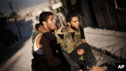시리아 알레포에서 정부군과 교전중 부상을 당한 동료를 후송하는 반군들