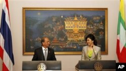 Visiting Myanmar President Thein Sein, left, shares a light moment with Thai Prime Minister Yingluck Shinawatra during a press conference at Government House in Bangkok, Thailand, Monday, July 23, 2012. (AP Photo/Rungroj Yongrit, Pool)