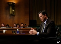 FILE - Then-FBI Director James Comey pauses as he testifies on Capitol Hill in Washington, before a Senate Judiciary Committee hearing, May 3, 2017.