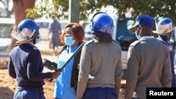 FILE - Police arrest a health worker during a protest against economic hardship and poor working conditions during the coronavirus disease (COVID-19) outbreak in Harare, Zimbabwe, July 6, 2020.
