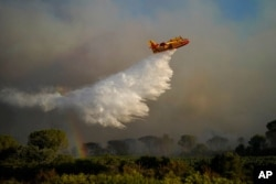An aircraft dumps water on a wildfire near Le Luc, southern France, Aug. 17, 2021.