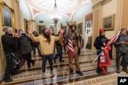 Supporters of President Donald Trump are confronted by U.S. Capitol Police officers outside the Senate Chamber inside the Capitol in Washington, Jan. 6, 2021.